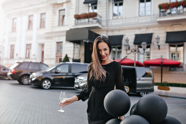 Retrato al aire libre de mujer despreocupada sosteniendo una copa de champán mientras está de pie en la calle