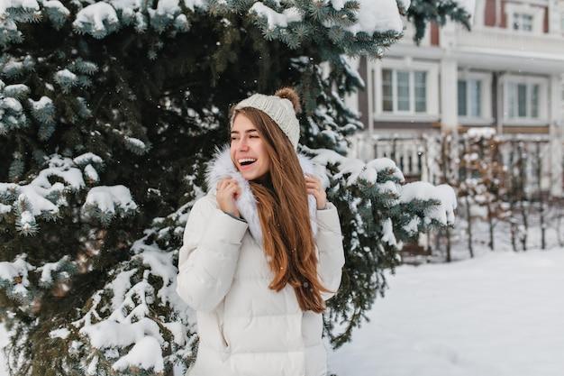Retrato al aire libre de mujer divertida con gorro de punto mirando a otro lado mientras posa cerca de abeto verde cubierto de nieve.