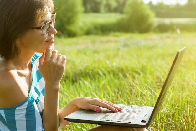 Retrato al aire libre mujer independiente, blogger. mira el monitor de la computadora portátil.