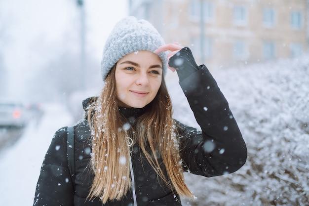 Retrato al aire libre de una mujer joven con chaqueta y gorro de punto, volviendo su rostro a los copos de nieve que caen. invierno, concepto de protección de la piel.
