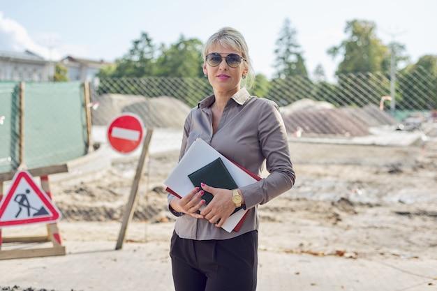 Retrato al aire libre de mujer madura de negocios, colocación de adoquines