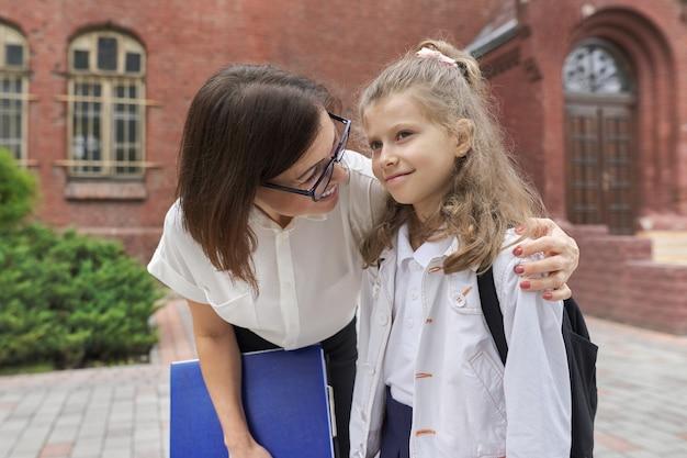 Retrato al aire libre de mujer maestra y niña estudiante juntos