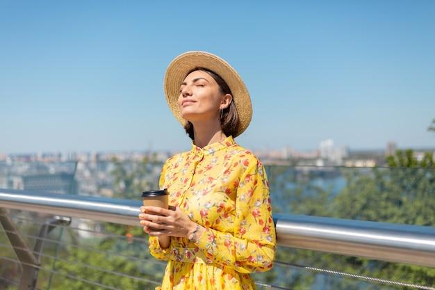 Retrato al aire libre de mujer con vestido amarillo de verano y sombrero con una taza de café disfrutando del sol, se encuentra en el puente con una vista increíble de la ciudad