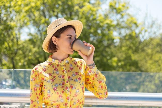 Retrato al aire libre de mujer en vestido amarillo de verano y sombrero con taza de café disfrutando del sol