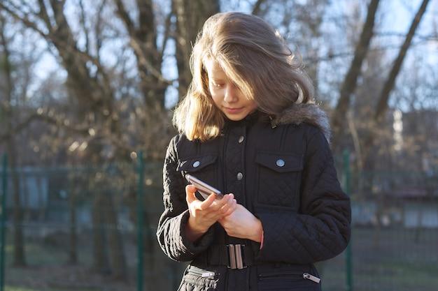 Retrato al aire libre niña de 8, 9 años con smartphone, chica de temporada de primavera en chaqueta