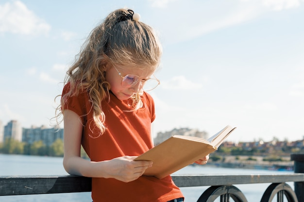 Retrato al aire libre de pequeña colegiala con libro