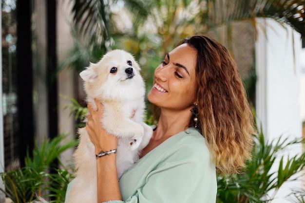Retrato al aire libre de rizado mujer bronceada europea sostiene feliz perro mascota pomerania spitz