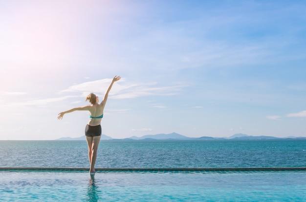 Retrato al aire libre del verano de la mujer bonita joven que mira al océano en la playa tropical