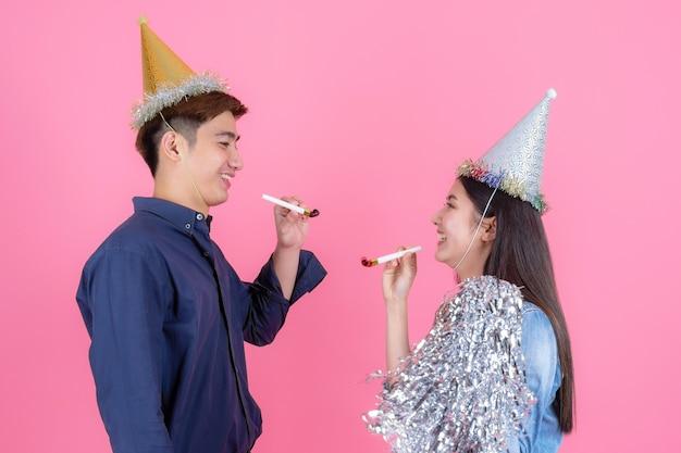 Retrato alegre adolescente hombre y mujer bonita con accesorios de fiesta, llevan sombrero de fiesta y juguetón disfrutando en rosa