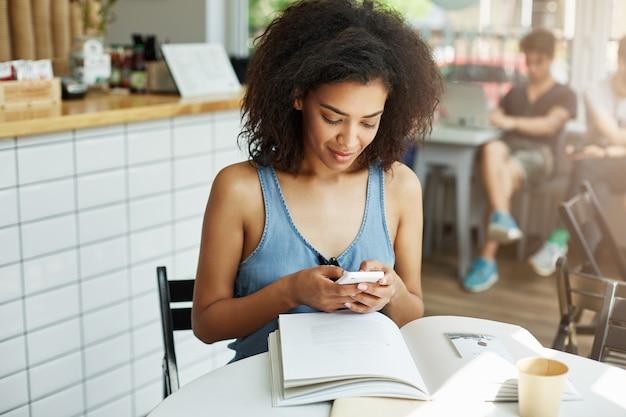 Retrato de una alegre y alegre mujer estudiante africana de piel oscura con cabello oscuro y rizado en camisa azul sentado en un café cerca de la universidad, leyendo un resumen académico, tomando café, conversando con su novio o