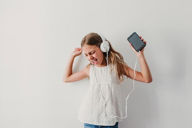 Retrato de una alegre chica adolescente linda escuchando música en el teléfono móvil y auriculares. bailando en casa concepto de felicidad, música y estilo de vida.