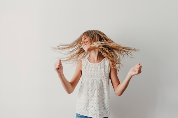Retrato de una alegre chica adolescente linda escuchando música en el teléfono móvil y bailando en casa. concepto de felicidad, música y estilo de vida.