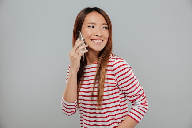 Retrato de una alegre chica asiática hablando por teléfono móvil