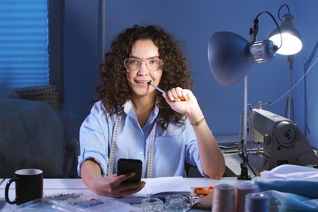 Retrato de alegre chica de diseñador se ríe y mira a cámara