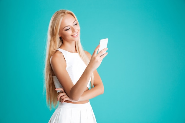 Retrato de una alegre chica rubia sosteniendo un teléfono móvil aislado en el fondo azul.