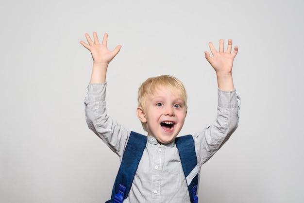 Retrato de un alegre colegial rubio con una mochila escolar