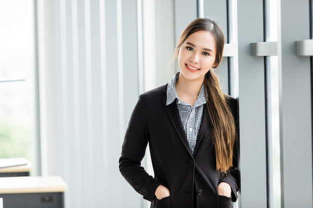 Retrato de una alegre empresaria asiática madura en la sala de oficina, el negocio expresó confianza envalentonada y concepto exitoso
