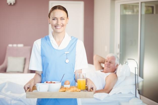Retrato de alegre enfermera con bandeja de pie en la habitación