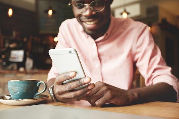 Retrato de alegre estudiante afroamericano escribiendo un mensaje en el teléfono inteligente