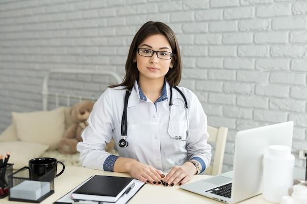 Retrato de alegre feliz doctora sentada en su lugar de trabajo