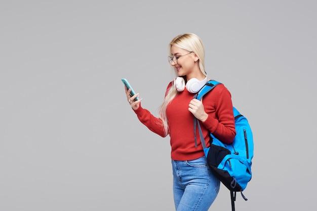 Retrato de una alegre feliz rubia estudiante con mochila azul escuchando la conferencia en línea en el teléfono con auriculares aislados sobre espacio gris. copie espacio para texto en el lado izquierdo