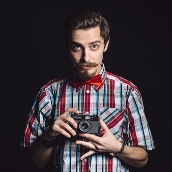 Retrato de un alegre fotógrafo en estudio