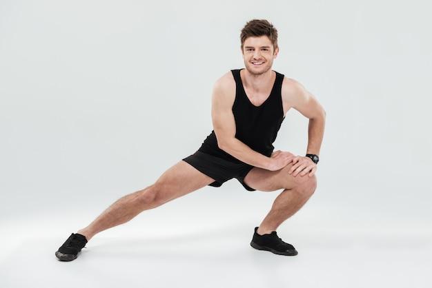 Retrato de un alegre hombre sano calentamiento antes del gimnasio