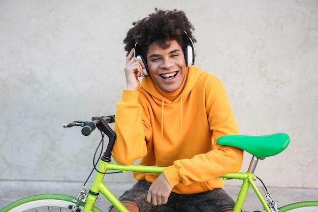 Retrato de alegre joven adolescente motociclista escuchando una lista de reproducción de música - centrarse en la cara