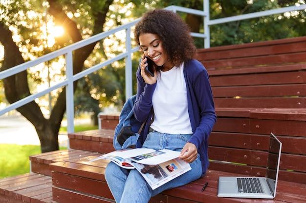 Retrato de una alegre joven africana con mochila hablando por teléfono móvil mientras descansa en el parque, leyendo una revista