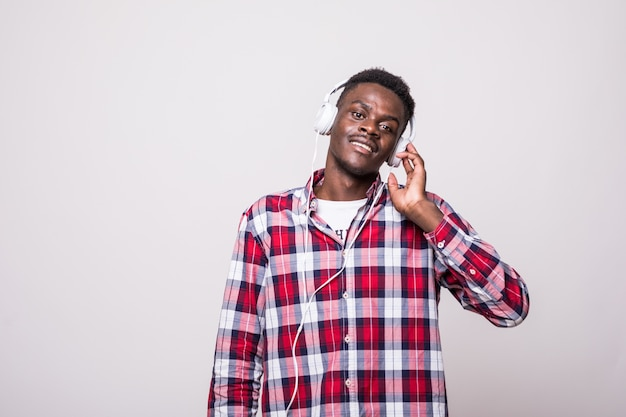 Retrato de un alegre joven afroamericano escuchando música con auriculares y cantando aislado