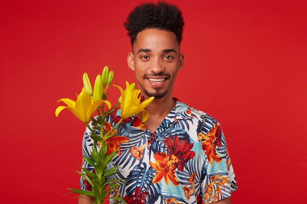 Retrato de alegre joven afroamericano, viste con camisa hawaiana, mira a la cámara con expresión feliz, se encuentra sobre un fondo rojo con flores amarillas y una amplia sonrisa.