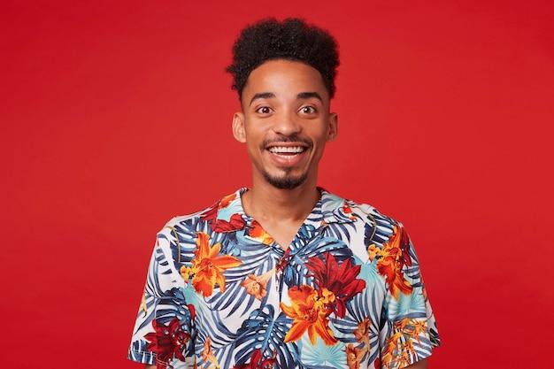 Retrato de alegre joven afroamericano, viste con camisa hawaiana, mira a la cámara con expresión feliz, se encuentra sobre fondo rojo y sonríe ampliamente.