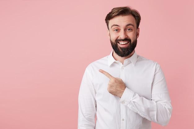 Retrato de alegre joven barbudo con cabello castaño corto de pie contra la pared rosa en ropa formal, apuntando a un lado con el dedo índice y sonriendo ampliamente