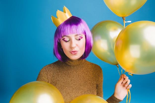 Retrato alegre joven con corte de pelo morado divirtiéndose. globos dorados, enviando un beso con los ojos cerrados, corona en la cabeza, vestido de lujo, gran fiesta, celebración.