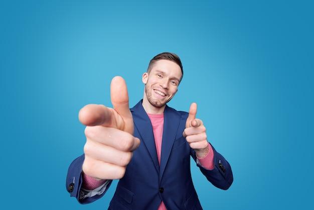 Retrato de alegre joven exitoso en chaqueta haciendo pistolas de dedos