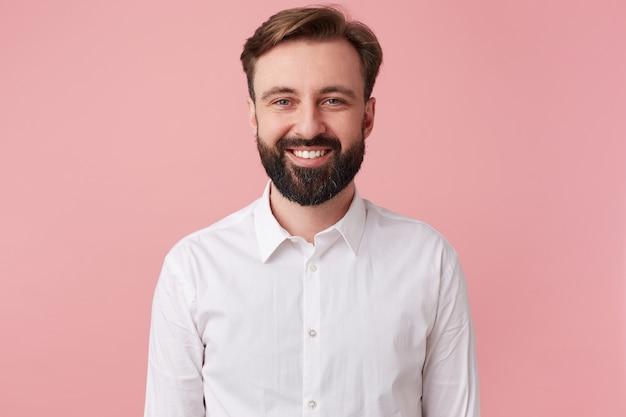 Retrato de alegre joven guapo barbudo, vestido con una camisa blanca. mirando a la cámara y sonriendo aislado sobre fondo rosa.