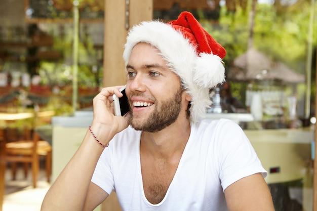 Retrato de alegre joven guapo con camiseta blanca y sombrero de santa claus hablando por teléfono móvil mientras disfruta de unas vacaciones en un país tropical
