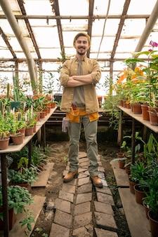 Retrato de alegre joven guapo cultivador de invernadero barbudo con cinturón de herramientas de jardinería de pie con los brazos cruzados en invernadero