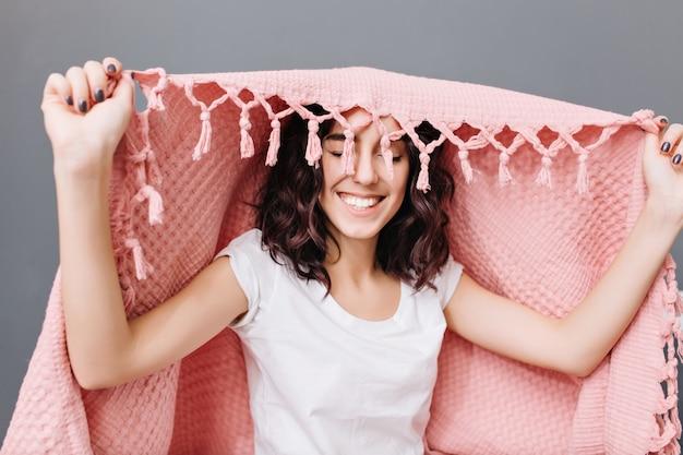 Retrato alegre joven morena en pijama divirtiéndose bajo una manta rosa. sonriendo con los ojos cerrados, expresando verdaderas emociones positivas, relajándose en casa