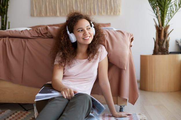 Retrato de una alegre joven mulata rizada sentada en la habitación, disfrutando de su canción favorita y leyendo una nueva revista sobre arte, mira pensativamente hacia otro lado y pasa un buen rato en casa.