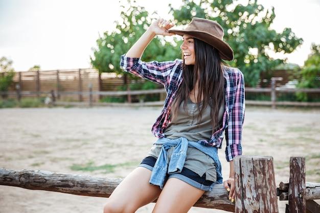 Retrato de alegre joven relajada vaquera sentada en la valla y sonriendo