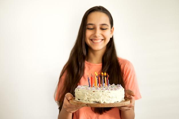 Retrato de alegre jovencita latina sonríe y sopla una vela en el pastel de cumpleaños. agitando la fiesta de cumpleaños feliz en casa. fondo de pared blanca.