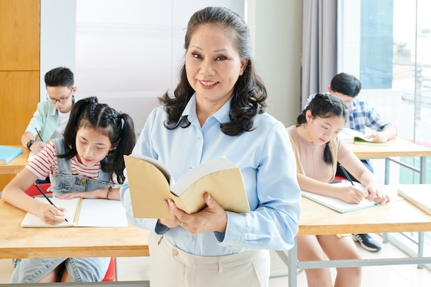 Retrato de alegre libro de lectura del maestro senior para estudiantes en clase