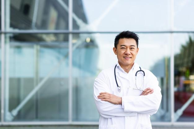 Retrato de alegre médico asiático sonriendo con las manos juntas en el fondo de la clínica moderna fuera mirando a la cámara