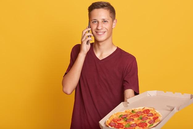 Retrato de alegre mensajero masculino comprueba la ruta a la casa del cliente a través de su teléfono inteligente