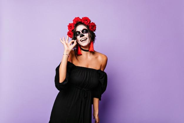 Retrato de alegre mexicano con aretes largos y accesorios rojos en traje para halloween. mujer de buen humor muestra signo ok