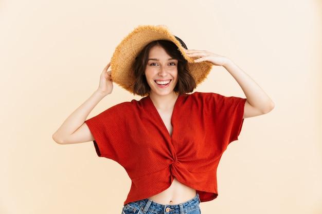 Retrato de alegre morena vacaciones mujer vistiendo sombrero de paja sonriendo aislado