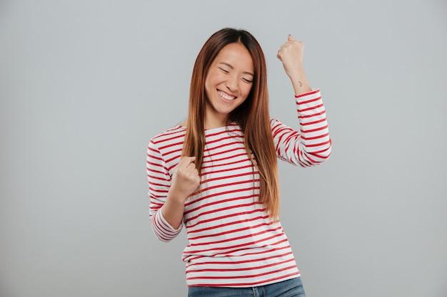 Retrato de una alegre muchacha asiática celebrando el éxito mientras está de pie