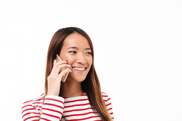 Retrato de una alegre muchacha asiática hablando por teléfono móvil