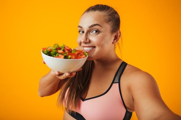 Retrato de una alegre mujer de fitness con sobrepeso vistiendo ropa deportiva que se encuentran aisladas sobre una pared amarilla, tomando un selfie con teléfono móvil, mostrando un tazón con ensalada